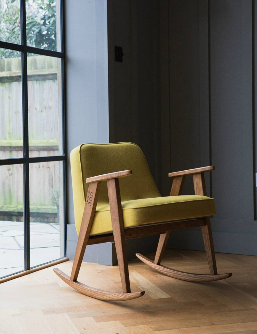 bujany fotel wżółtym kolorze przy dużym oknie iczarnej ścianie