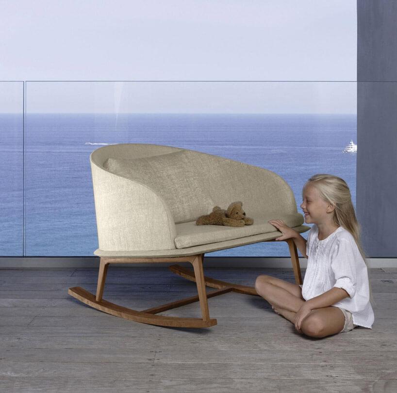 dziecko zmisiem na bujanym fotelu przy oknie zmorzem