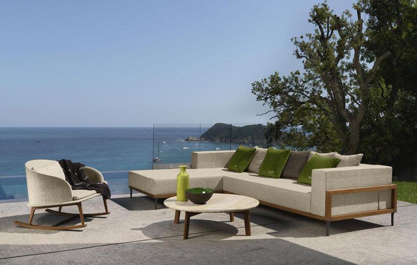 duża sofa zfotelem izielonymi poduszkami na tle morza