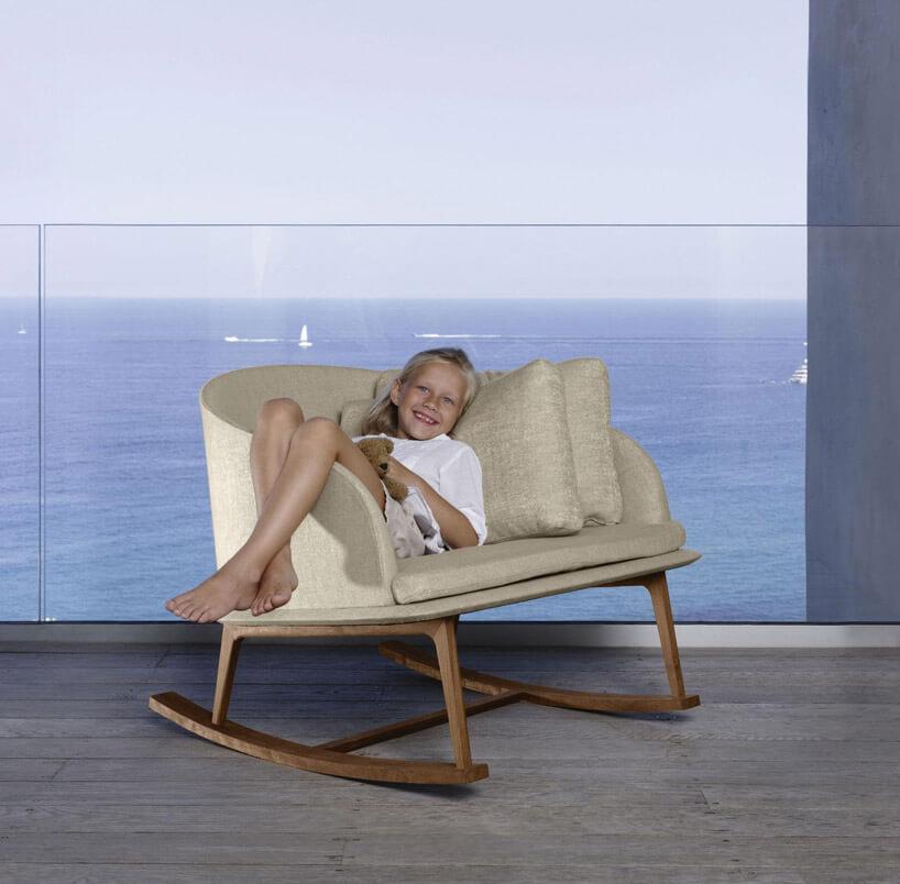 dziewczynka leżąca jasnym materiałowym fotelu na płozach