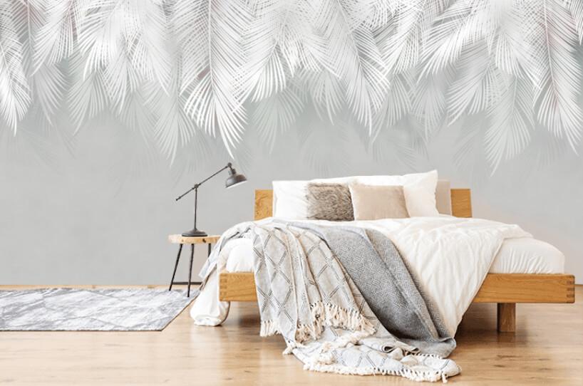 sypialnia zdużym drewnianym łózkiem na tle szaro białej tapety zmotywem dużych piór od Uwalls