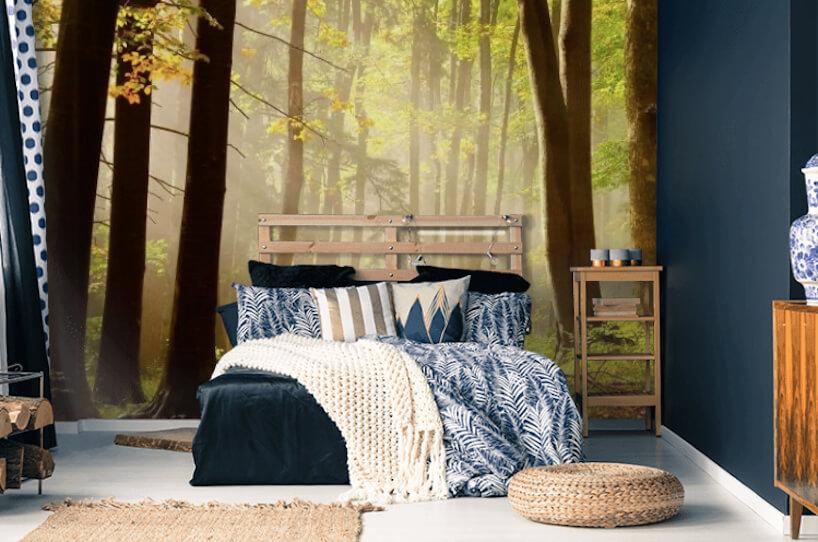 nowoczesna sypialnia zdrewnianymi meblami idużym drewnianym łóżkiem na tle tle fototapety zmotywem lasu od Uwalls