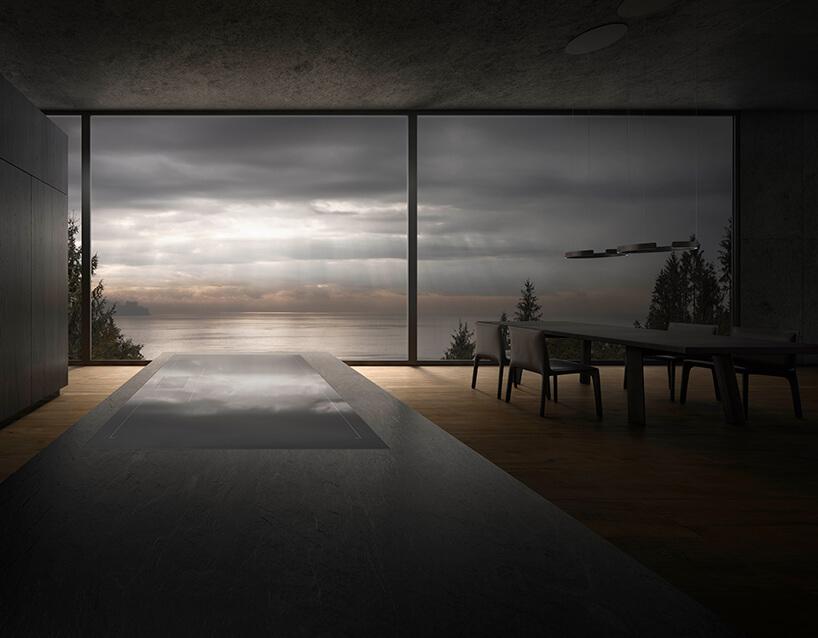 elegancka płyta indukcyjna Gaggenau wczarnym kamiennym blacie na tle przeszkloonej ściany zwidokiem na zachmurzone jezioro