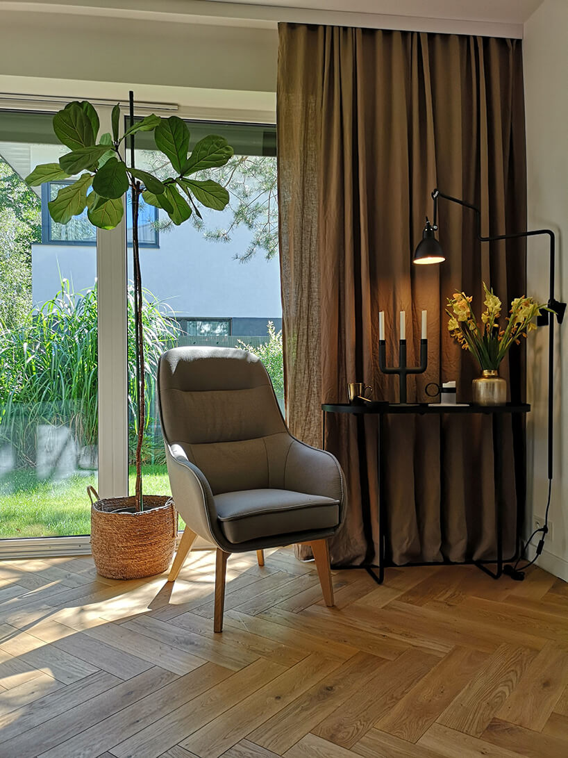 szary fotel Dot II od Gala Collezione na drewnianych nogach wpokoju zdrewnianą podłogą obok czarnego wysokiego stolika