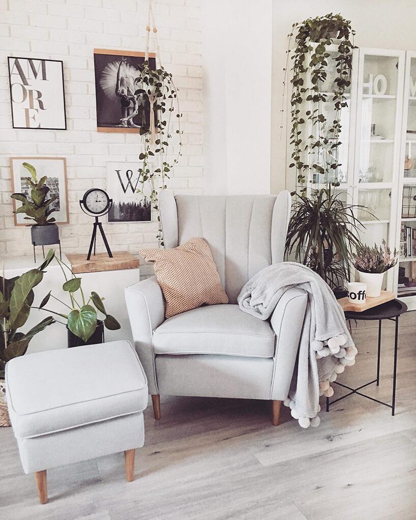 szary fotel Fido od Gala Collezione na drewnianych nogach stojący wbiałycm salonie obok szarej pufy
