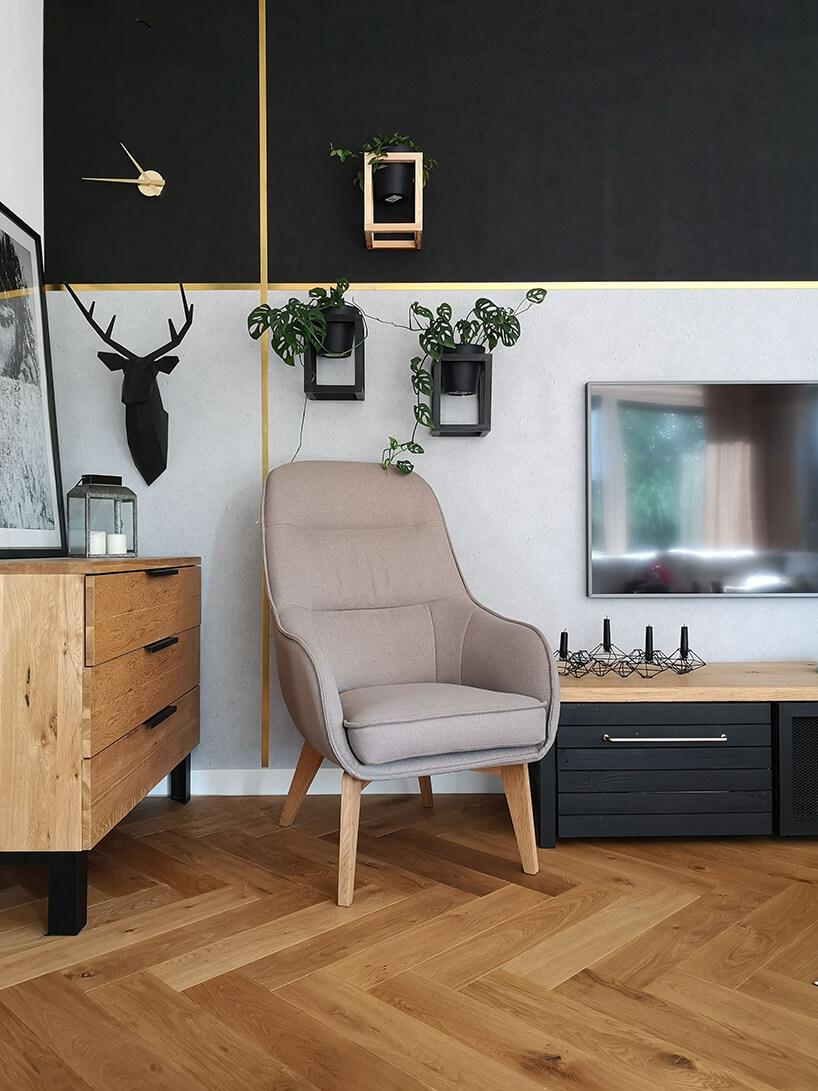 elegancki beżowy fotel Dot II Gala Collezione na drewnianych nogach waranżacji salonu zszaro czarną ścianą ze złotymi liniami