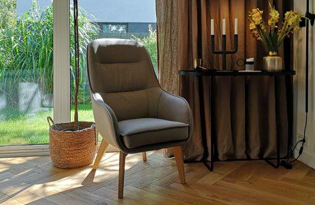 szary fotel Dot II od Gala Collezione na drewnianych nogach w pokoju z drewnianą podłogą obok czarnego wysokiego stolika