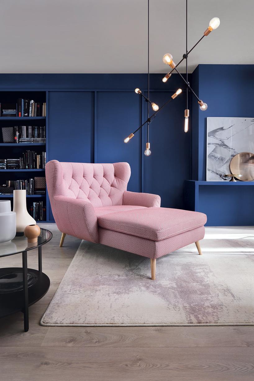 jasno różowy Szezlong Lord Gala Collezione na tle wnętrza zciemno niebieską ścianą