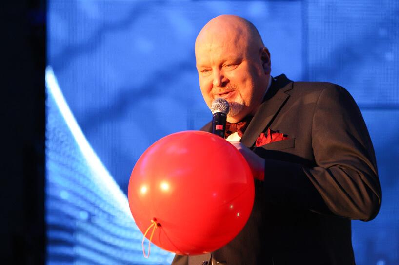 mężczyzna zmikrofonem trzymający czerwony balon podczas Siemens Future Living Award 2018