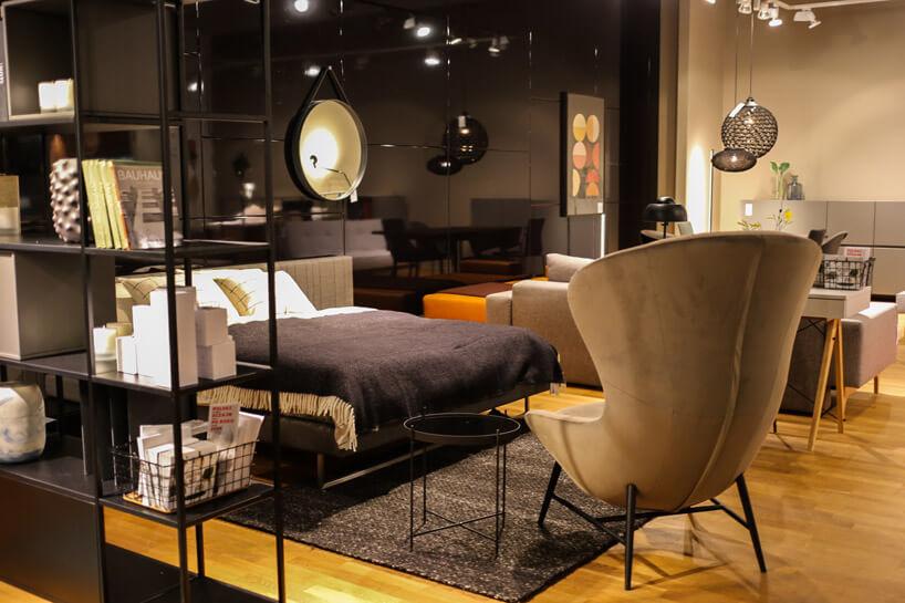 krzesło na cienkich czarnych nóżkach obok dużego łóżka