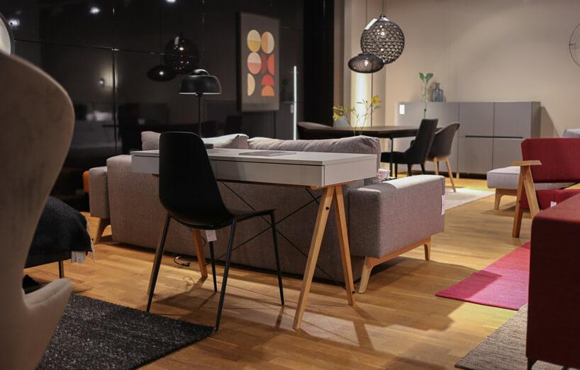 czarne krzesło przy małym szarym biurku na drewnianej podłodze