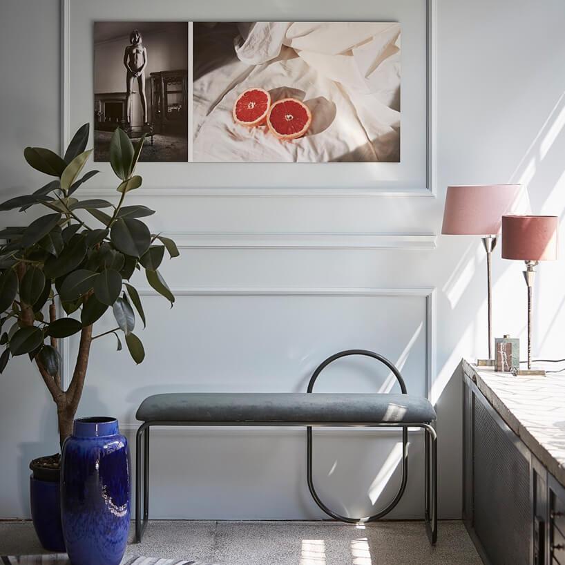 wnętrze galerii Ornament niebieski wazon iosłona na doniczkę obok szarej ławki pod obrazem zkobietą obok przekrojonego grejfruta