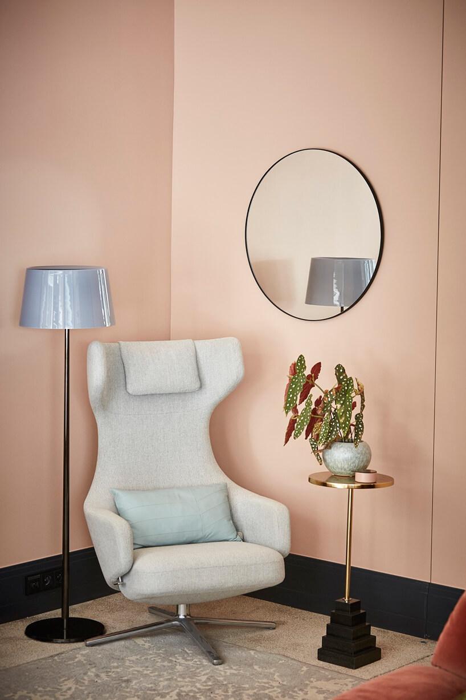 wnętrze galerii Ornament biały fotel zwysokim oparciem obok czarnej lampy zniebieskim kloszem iwyjątkowego czarno złotego stolika