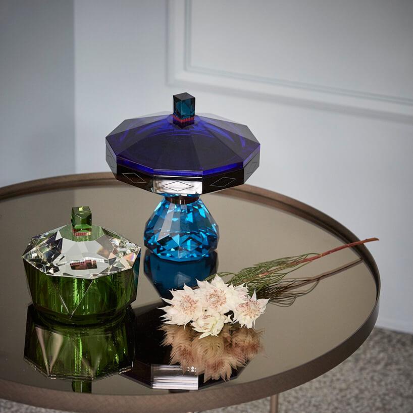 wnętrze galerii Ornament zielona iniebieska kryształowa cukiernica na okrągłym stoliku zlustrzanym blatem