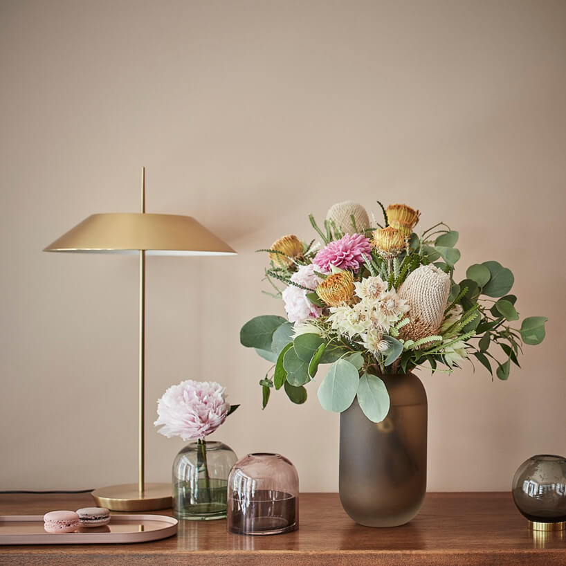 wnętrze galerii Ornament wyjątkowa złota lampka na drewnianym blacie komody obok szklany wazonów