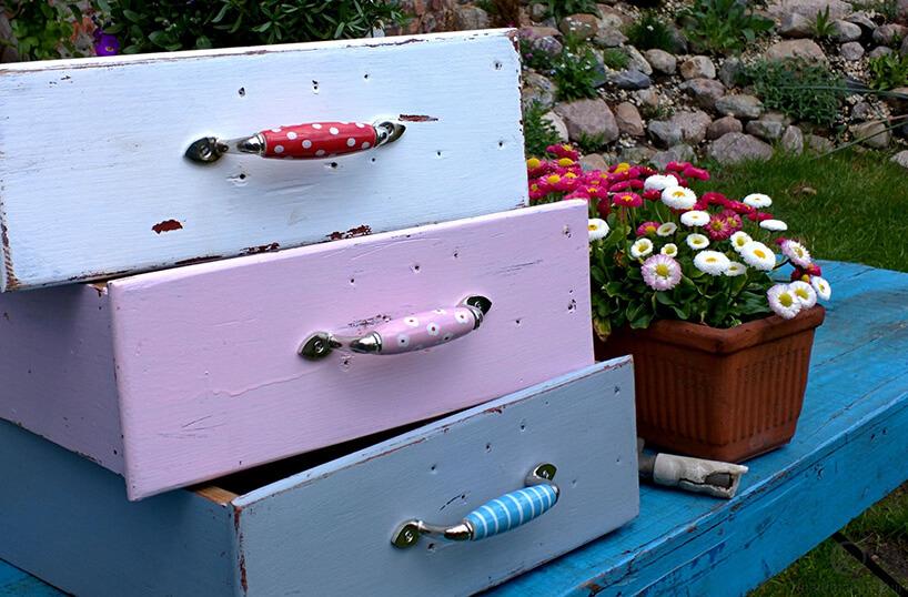 trzy kolorowe szuflady zpodłużnymi uchwytami