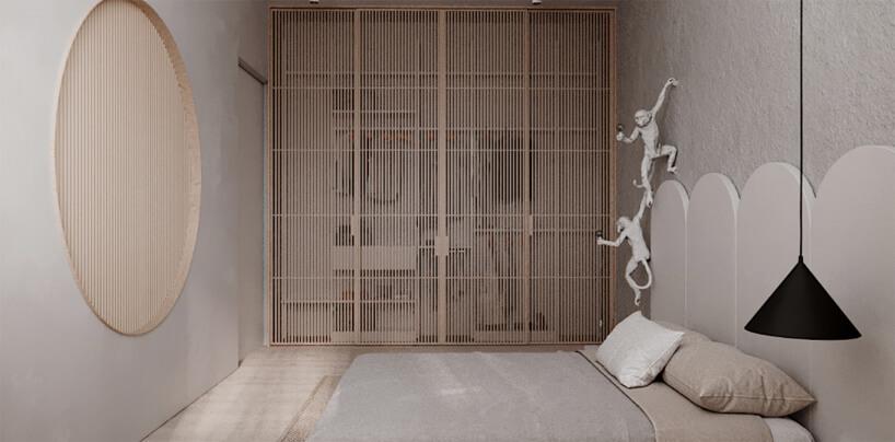 ciemno beżowa garderoba wsypialni od Hilight Design zfrontem zcienkich listewek obok lampy na ścianie wkształcie małp