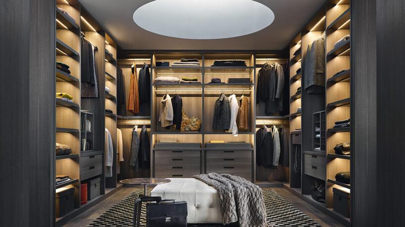 garderoba zciemną zabudową zbiałym plisowanym siedziskiem po środku ciemnej drewnianej podłogi