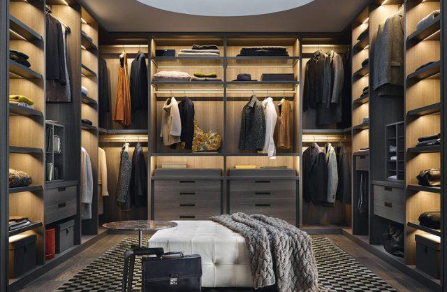 garderoba z ciemną zabudową z białym plisowanym siedziskiem po środku ciemnej drewnianej podłogi