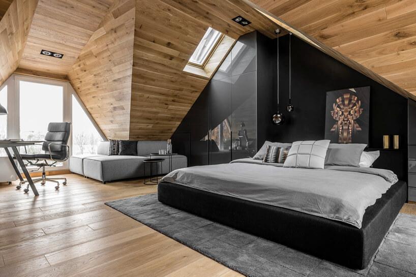 czarne łóżko na brązowym poddaszu
