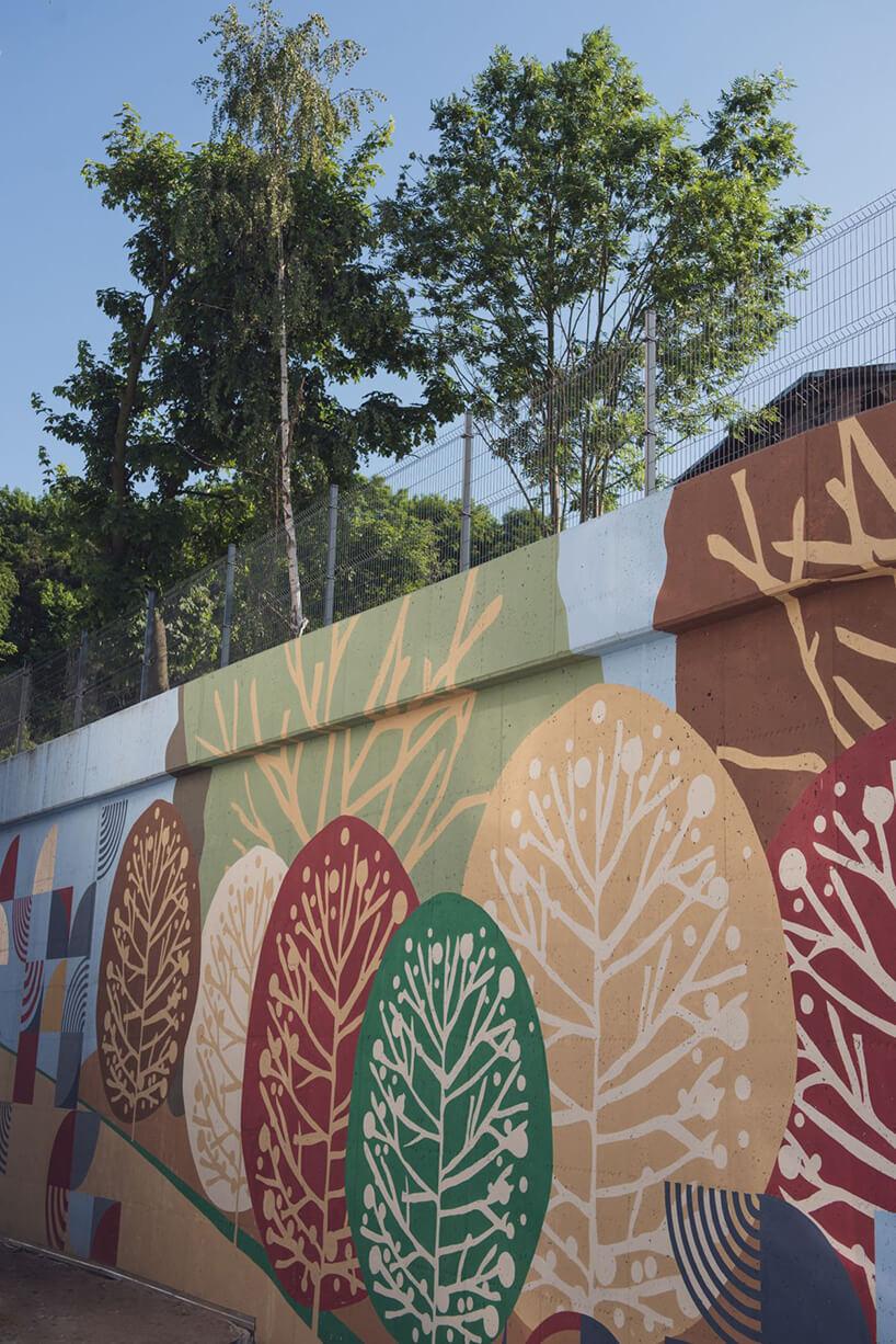 betonowa ściana pomalowana wmotyw drzew na osiedli Vialo wstylu hygge