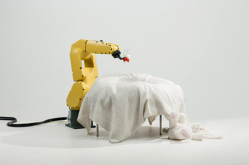 żółte ramię robota trzymające butelkę mleka na łózeczkiem