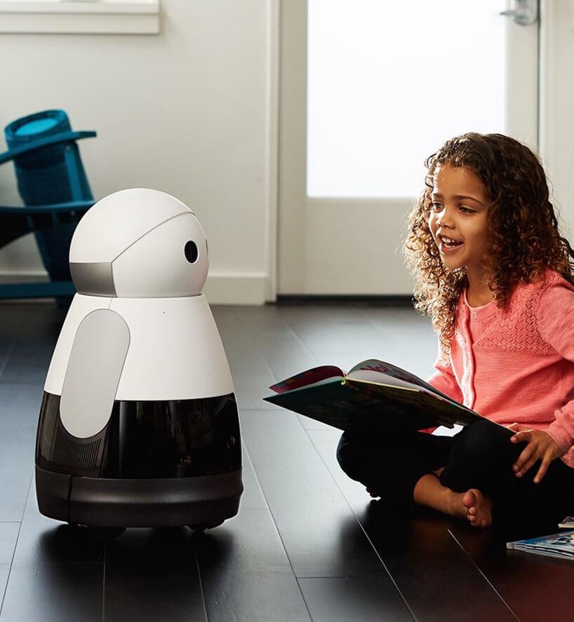 dziecko trzymające książkę isiedzące obok biało-czarnego robota