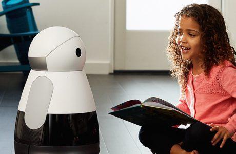 dziecko trzymające książkę i siedzące obok biało-czarnego robota