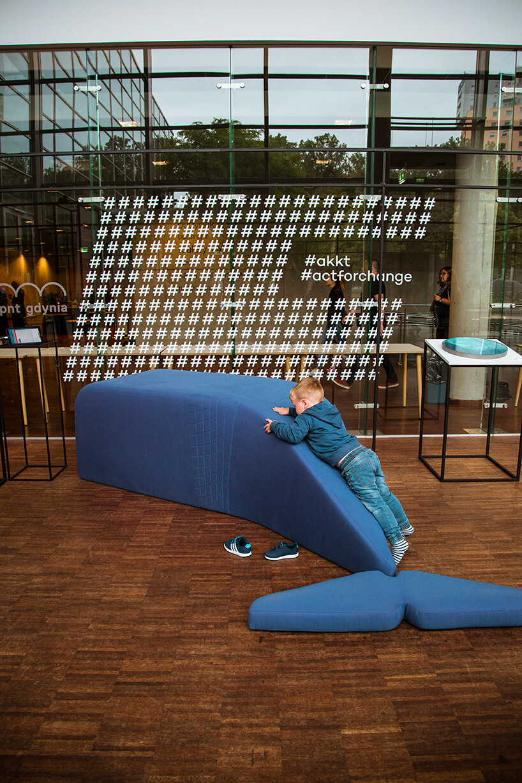 dziecko na niebieskim siedzisku wkształcie wieloryba przy prezentacji #akkt na Gdynia Design Days 2019