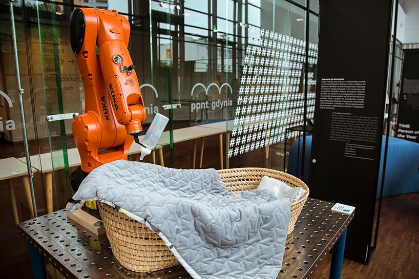 ramię robota automatycznego trzymające butelkę do karmienia dzieci na wiklinowym łóżeczkiem na Gdynia Design Days 2019