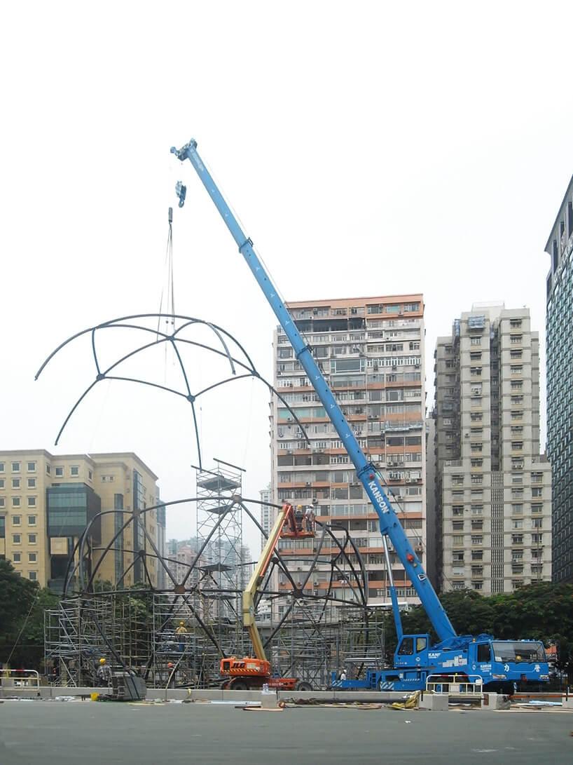 niebieski dźwig podnoszący metalową konstrukcję