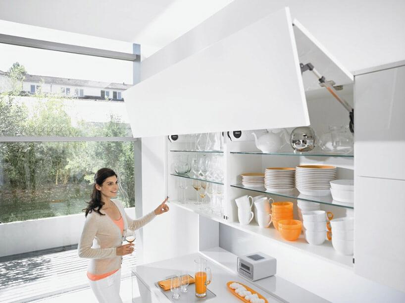 kobieta przy białej szafce otwieranej automatycznie