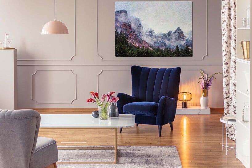 wnętrze salonu ze sztukaterią na szarej ścianie zobrazem górskim
