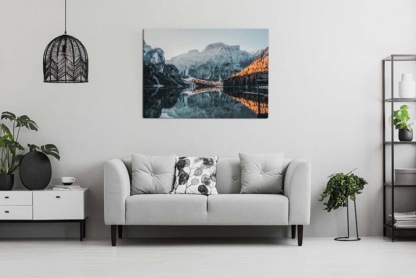 gładka jasno szara ściana zobrazem zpejzażem górskim przy szarej kanapie