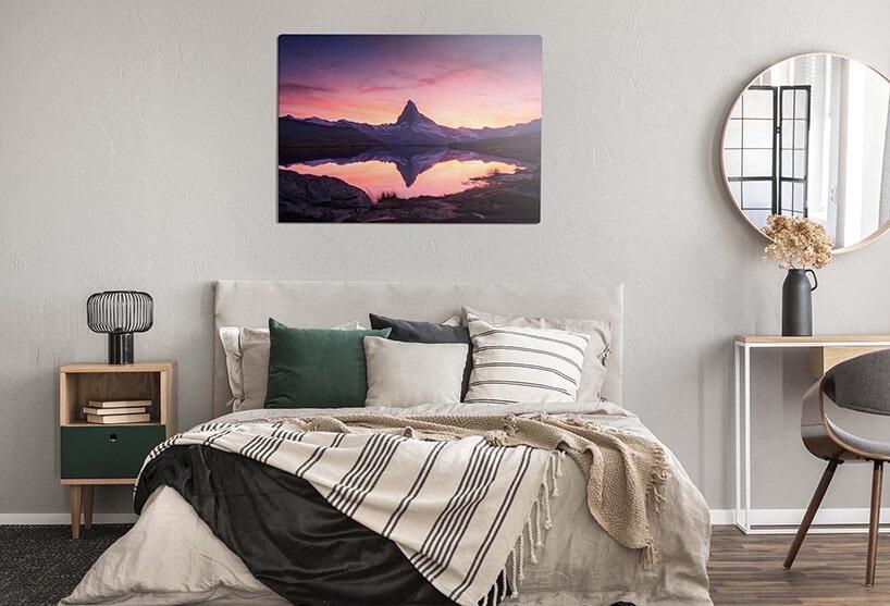 łóżko zsypialni zzielonymi poduszkami oraz obrazem górskim na ściane