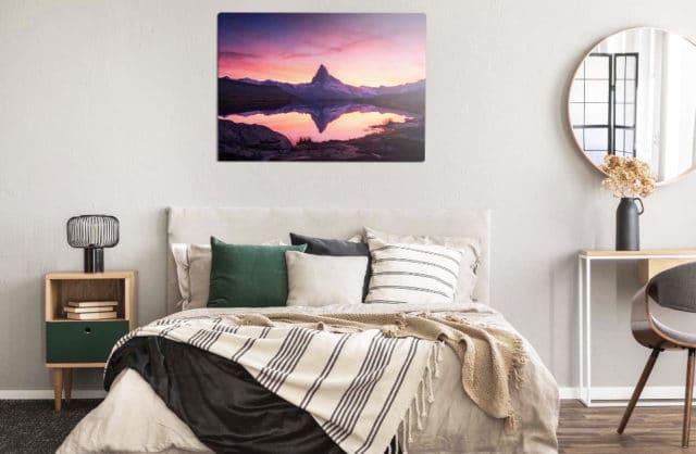 łóżko z sypialni z zielonymi poduszkami oraz obrazem górskim na ściane