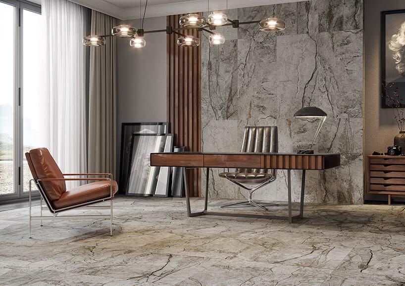marmurowe kafle wyłożone wgabinecie zstylowym drewnianym biurkiem oraz fotelami zbeżowej skóry