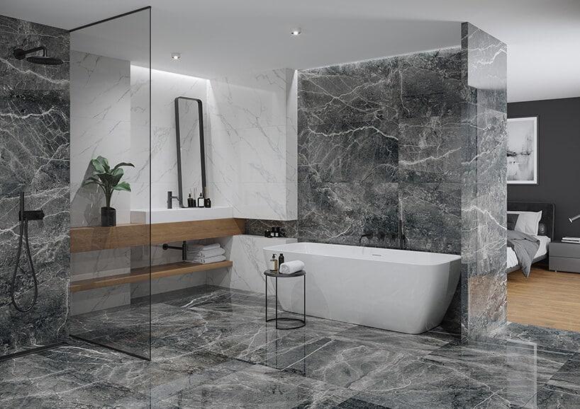 biała wanna wolnostojąca wwydzielonym pokoju kąpielowym wsypialni ze szklaną ścianą
