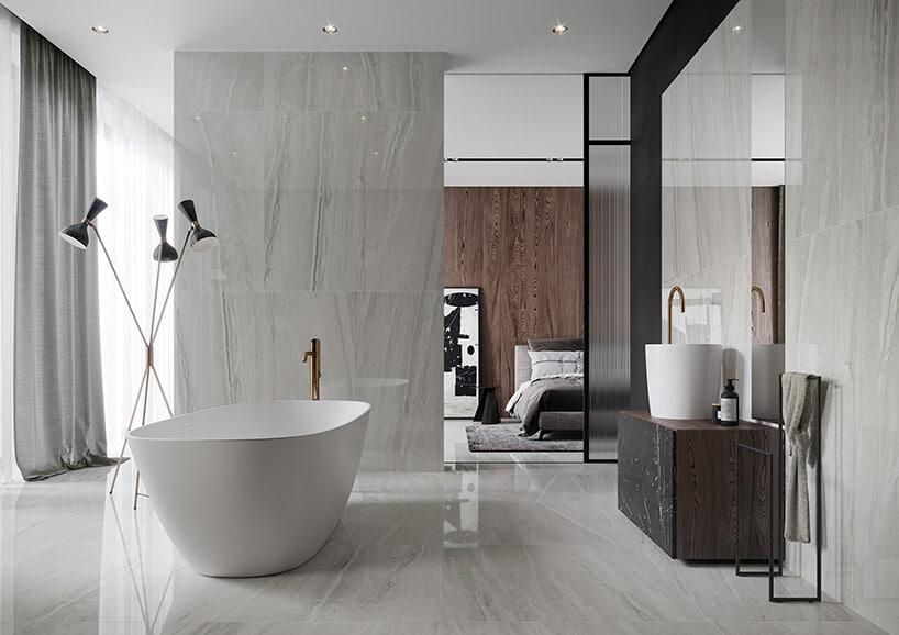 pokój kąpielowy zkaflami zimitacją jasne popielatego drewna przy wannie ibiałej umywalce na drewnianej szafce