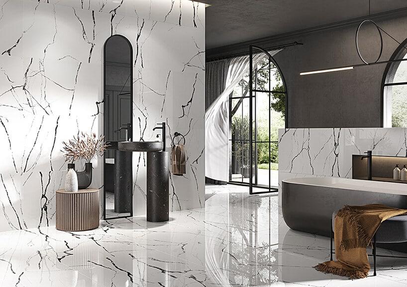 biała łazienka zkaflami wczarne proste plamki oraz dodatki szarych akcesoriów