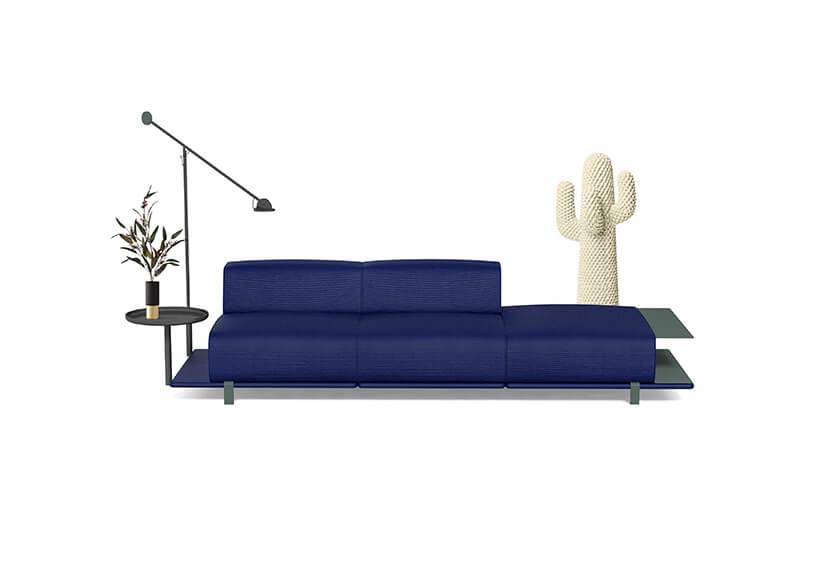 niebieska sofa zniskim oparciem ze stolikami po bokach ilampą od MK Design
