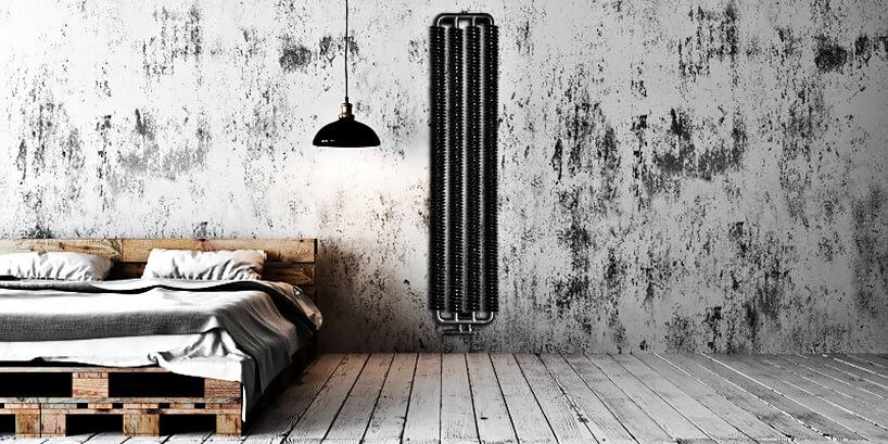 czarny grzejnik pionowy do loftów obok łóżka na paletach
