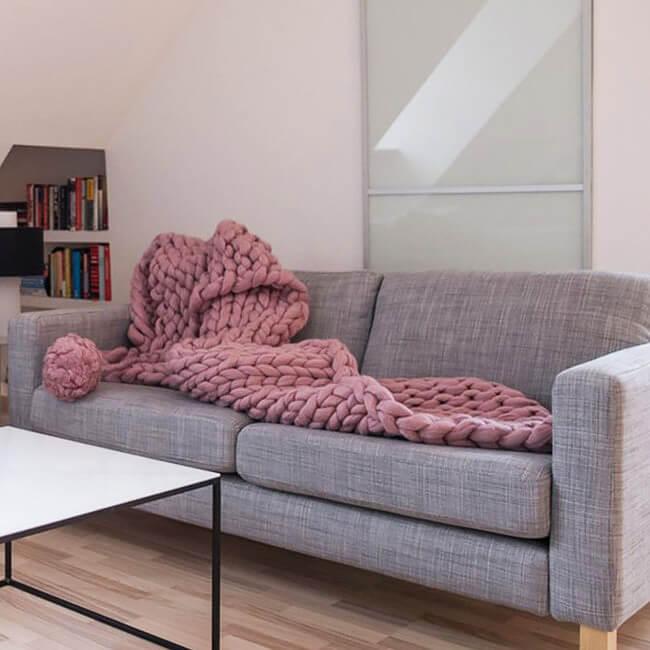 różowy dziergany koc na sofie