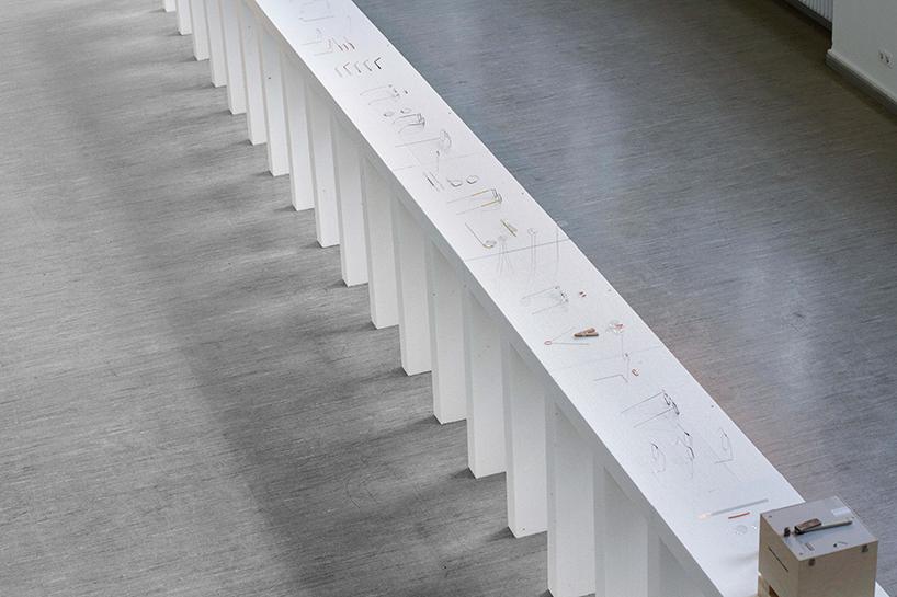 """długi biały stół jako prezentacja projektu """"The One Dollar Glasses"""" tanie okulary"""