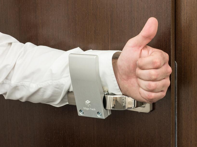 mężczyzna wbiałej koszuli przy brązowych drzwiach znakładką na klamkę od Gligo-Tech