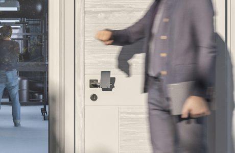 mężczyzna przy beżowych drzwiach z nakładką na klamkę od Gligo-Tech