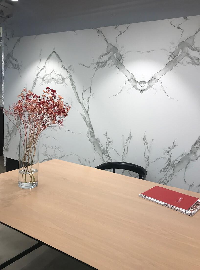 biurko zwazonem na tle białej kamiennej ściany Cosentino