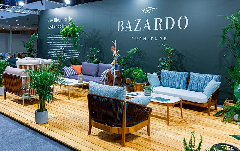 stoisko Bazardo furniture zróżnymi siedziskami na drewnianych deskach pośród roślin
