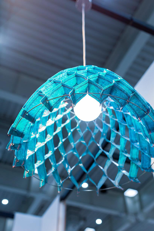 wyjątkowa niebieska lampa wisząca od Bozzetti zkloszem zpojedynczych pasków zszytych wromby