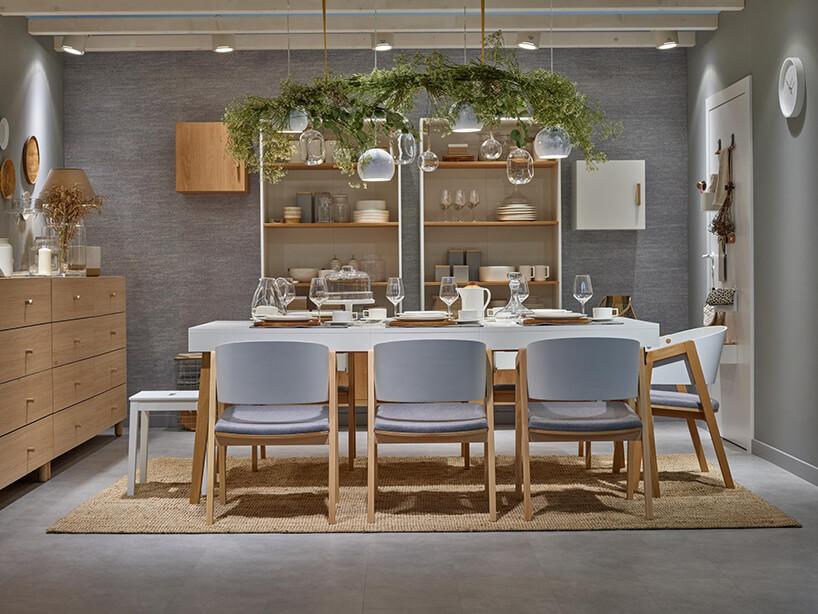 aranżacja jadalni wjasnym brązie zdużym białym stołem zkrzesłami drewnianymi od VOX
